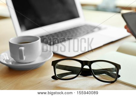 Businessman working place with laptop, glasses and cup of coffee