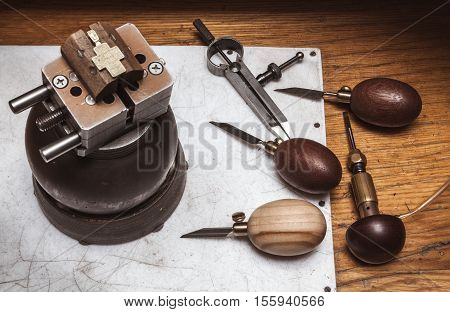 Cross in bullseye vise, gravers and compasses