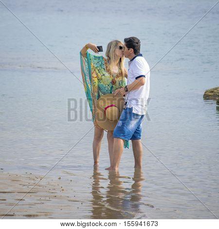 PORTO GALINHAS, BRAZIL, JANUARY - 2016 - Young adult couple kissing at shore of beach in Porto Galinhas Pernambuco Brazil