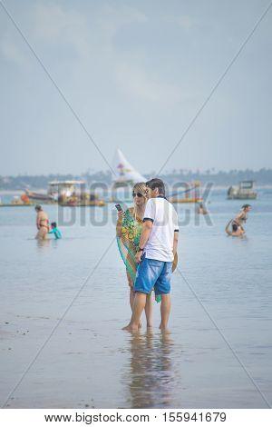PORTO GALINHAS, BRAZIL, JANUARY - 2016 - Young adult couple at shore of beach in Porto Galinhas Pernambuco Brazil