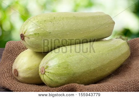 three courgettes on sackcloth with a blurred background.