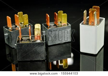 Auto electronic collection on black background. Car electromagnetic relay switch. Car automotive sensor, bokeh