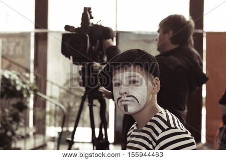Minsk Belarus - November 11 2016: Sad boy actor mime in the background videographer