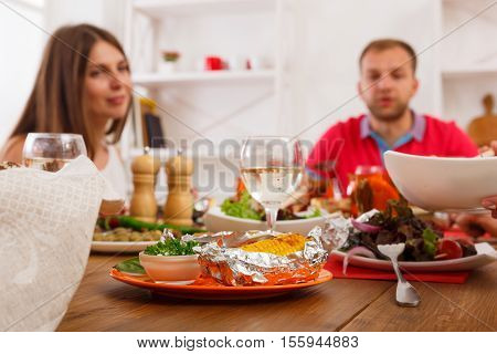 Friends meeting. Served table at dinner party, people unfocused, eating healthy meals at party dinner table in cafe, restaurant. Company celebrates with grilled corn food at wooden table indoors.
