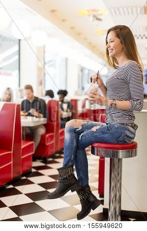 View of the young woman drinking coffee in the diner
