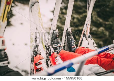 Four unrecognizable skier driving on ski lift. Focus of a skis.