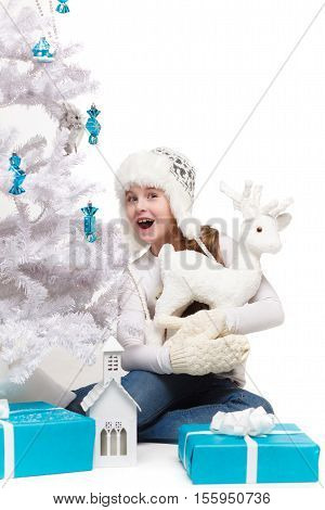 beautiful little girl holding a white fawn figurine on the background of Christmas tree