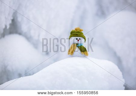 snowman in hat and scarf is standing on fascinating fluffy snow near the hill and around there are frozen textured patterns.