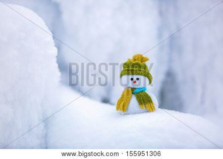 Incredible beautiful interesting white snow froze in strange textures forms and snowflakes and among all this beauty there is a little snowman in a hat and scarf.