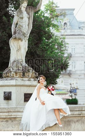Wedding photo shooting. Bride sitting near monument in the city. Holding bouquet and smiling. Wearing white dress, white shoes and veil. Outdoor, full body