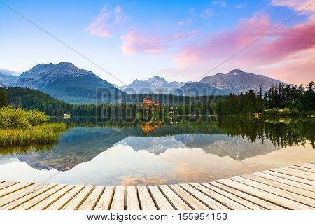 An old pier reveals views of the charmed lake green mountains with the mighty peaks and blue sky with cloud.Strbske Pleso lake Slovakia Tatra mountains