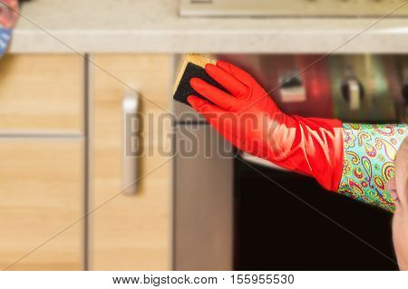 Woman makes chores in the kitchen at home cleaning in gloves with a sponge. Cropped view.