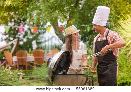 Happy couple cooking meat on barbecue grill, France