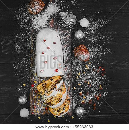 Christmas stollen. Traditional German European festive dessert. Ingredients red cranberries pine nuts for Christmas cake Stollen. Stollen cake is cut into pieces. Christmas food card. Top view Black background