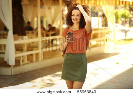 Attractive woman savouring coffee and walking on the street