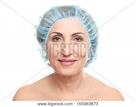 Senior woman in surgeon cap on white background