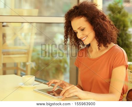 Attractive woman savouring coffee and using tablet in cafe