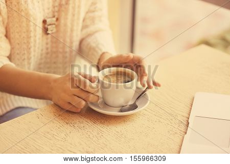 Female hands holding cup of coffee and sitting at table in cafe