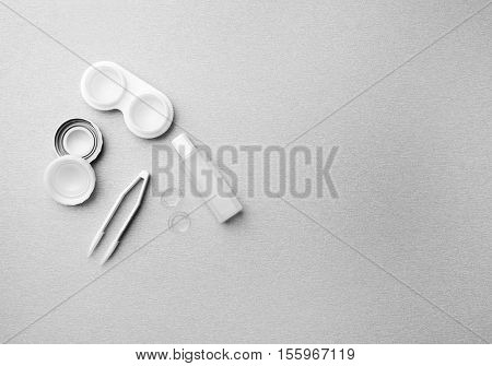 Pair of contact lenses, container, tweezers and bottle with solution on grey background, close up view
