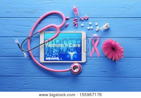 Tablet with text WOMANS CARE, pills and stethoscope on blue wooden background