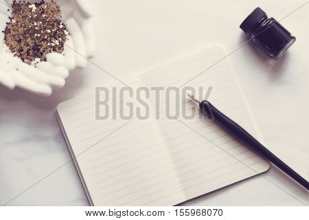 Over head flat lay desktop. White, vintage décor. Pen and ink. Open notebook, gold glitter.