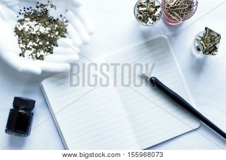 Over head flat lay desktop. White, vintage décor. Pen and ink. Open notebook, office supplies and gold glitter