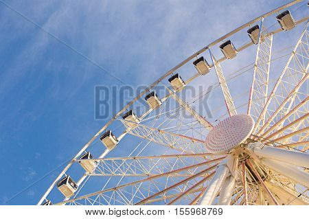 Ferris wheel against a blue sky with whispy clouds