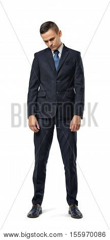 A miserable businessman full-height looking down isolated on the white background. Business and management. Poses and gestures. Failures and depression.