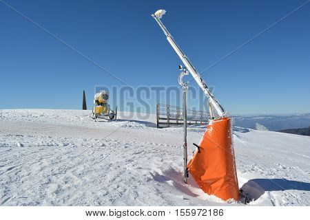 Start of the ski slopes with ramp high wooden fence snow cannon and meteorological wind gauge mounted on the ramp