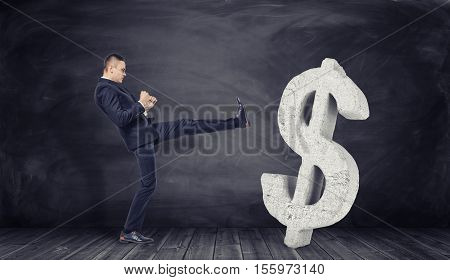 Businessman in full growth kicks off a huge concrete dollar sign on a black background. Refusal of the money. To have your own opinion. Financial independence. Rejection of the loan.