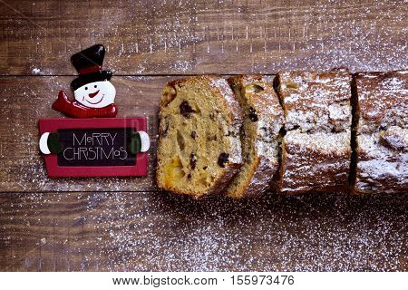 high-angle shot of a fruitcake on a rustic wooden table sprinkled with icing sugar and a snowman-shaped chalkboard with the text merry christmas written in it