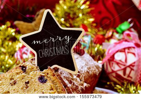 closeup of a fruitcake topped with a star-shaped signboard with the text merry christmas, on a table full of christmas gifts and ornaments
