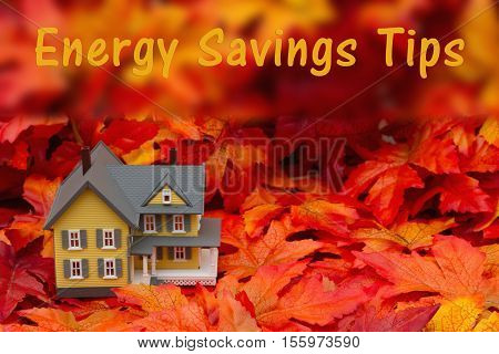 Home energy savings tips in the fall season Some fall leaves and yellow and gray house with text Energy Savings Tips