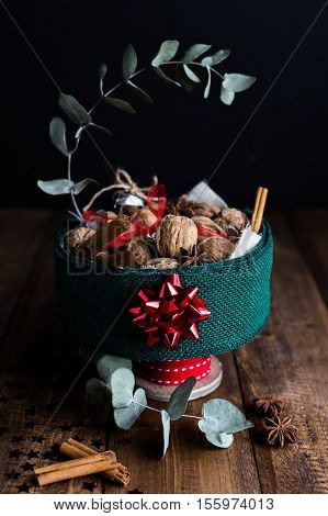 A Festive Table Centrepiece Full of Walnuts, Cinnamon Sticks and Star Anise, decorated with Ribbon and Eucalyptus on Rustic Wooden Table