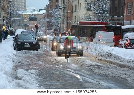 STOCKHOLM SWEDEN - NOV 10 2016: Snow chaos in the traffic in central Stockholm. Cars busses and bicycles. November 10 2016 in Stockholm Sweden