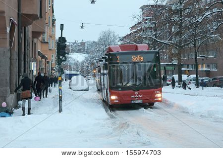 STOCKHOLM SWEDEN - NOV 10 2016: Snow chaos in the traffic in central Stockholm. Cars busses and people. November 10 2016 in Stockholm Sweden