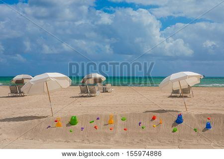 White and grey umbrellas and lounge chairs in the trendy and popular South Beach in Miami USA