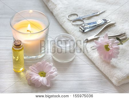 spa nail care with aroma candle, flower on wooden background