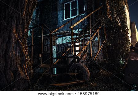 Two-storey house with a staircase overgrown with ivy night.