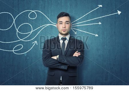 A businessman with folded arms standing near a blue wall and the drawn arrows goes through his head. Queueing up one's thoughts. Open to new ideas and opportunities. To get business in order.