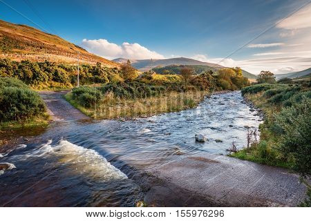 River crossing on College Burn and The Cheviot, from which the hill range takes its name, and is the highest point in Northumberland located in the Anglo-Scottish borders, seen here in autumn from College Valley