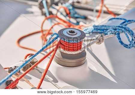 Tangled ropes on the winch on a yacht on background port and blue water