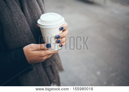 Young woman is drinking coffee on the street. Close-up of hands with white take away cup of coffee. Early morning routine. Hot cup of coffee while walking outside on cold winter day. Copy-space blank for your advertisement text or design content