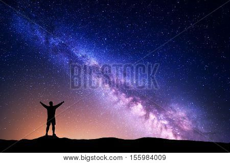 Purple Milky Way with silhouette of a standing man with raised up arms on the hill. Night landscape with beautiful galaxy. Universe. Night starry sky with Milky Way and yellow light poster