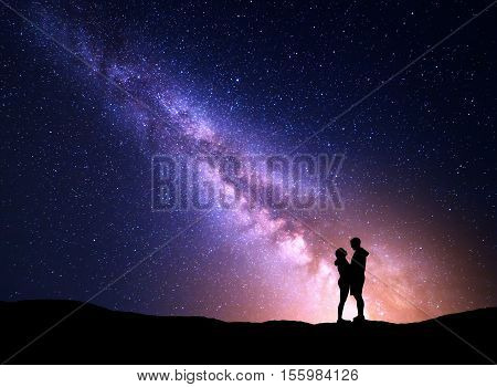 Milky Way with silhouette of people. Landscape with night starry sky. Standing man and woman on the mountain with yellow light. Hugging couple against purple milky way. Beautiful galaxy. Universe