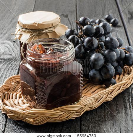 Red onion jam (onion confiture) with grapes in glass jars in a wicker basket on a wooden table. French cuisine. Square image