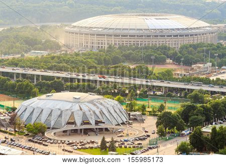 Moscow, Russia - June 20, 2016: Reconstruction of Luzhniki Stadium and Druzhba Multipurpose Arena for soccer world cup 2018 in Luzhniki, Moscow. Bridge Luzhniki, transportation, heavy traffic, cars, parking spaces (view from above) in Moscow, Russia