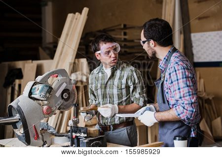 Two men builder with circular saw having a conversation. poster