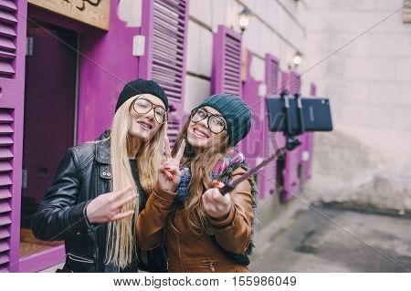 two beautiful girls are photographed on the street in hats and classy jackets