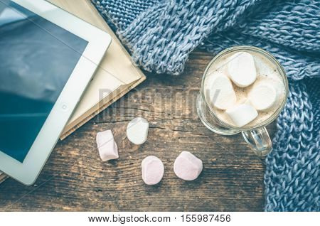 Cozy winter home background glass of hot cocoa with marshmallow book digital tablet and warm knitted scarf on an old wooden table. Coffee break in the morning. Top view. Copy space.